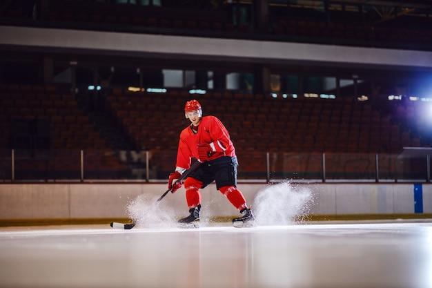 Positiver hübscher kaukasischer hockeyspieler, der mit stock in den händen skatet.