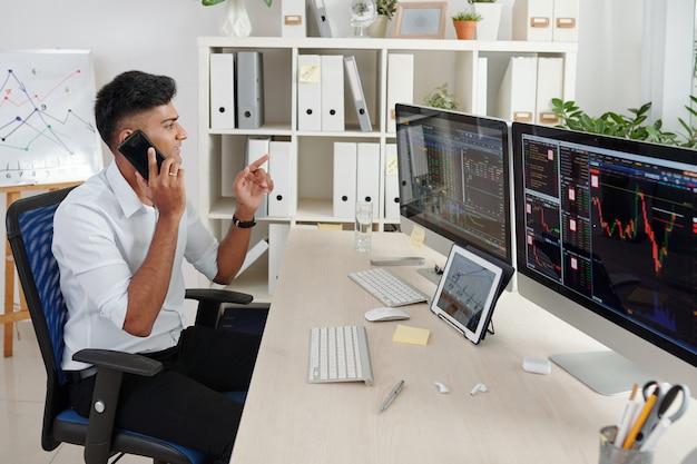 Positiver indischer händler, der aktiendaten auf computerbildschirmen analysiert und kunden telefonisch berät