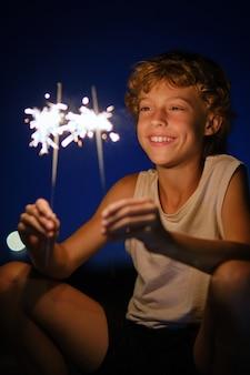 Positiver junge, der urlaub mit wunderkerzen feiert