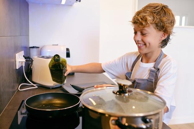 Positiver junge mit olivenöl, der in der küche kocht