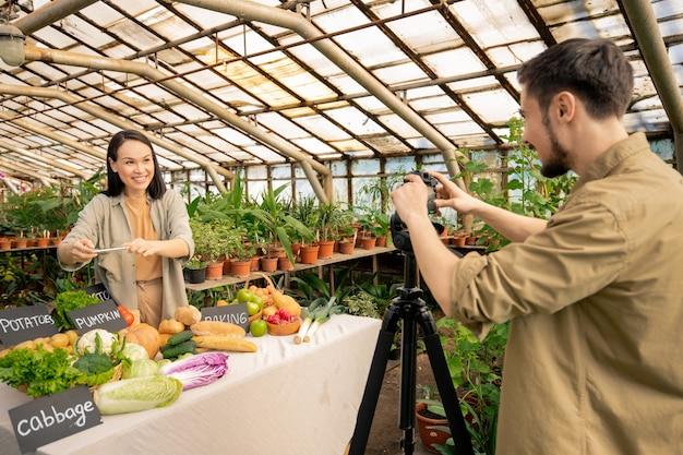 Positiver junger asiatischer blogger, der gemüse auf smartphone fotografiert und es in der ernährungs-app scannt, während video mit betreiber macht