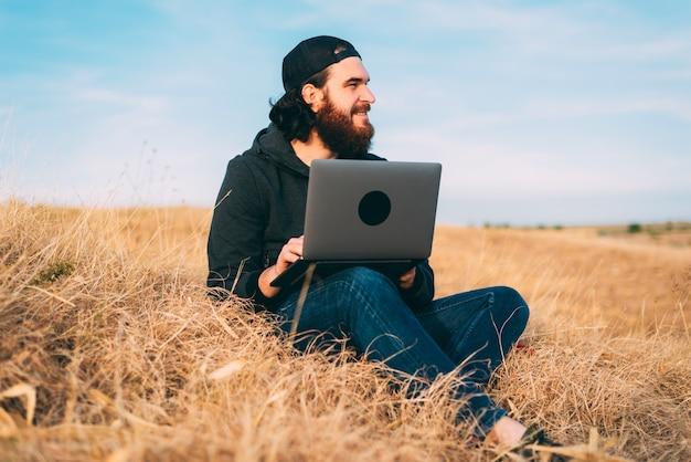 Positiver junger bärtiger mann, der am computer auf einem feld arbeitet