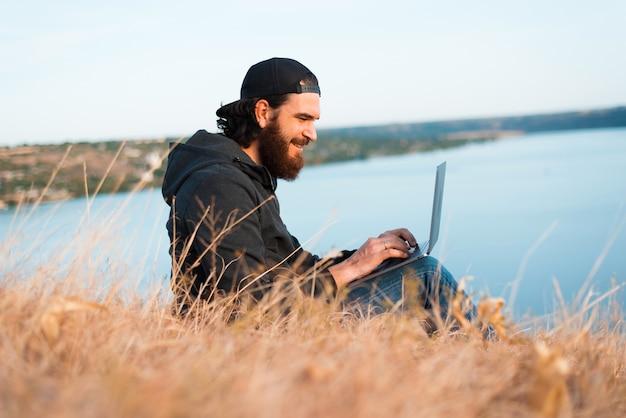 Positiver junger bärtiger mann, der im computer auf dem feld nahe einem fluss arbeitet und schaut