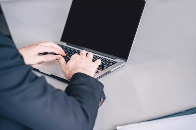 Positiver junger geschäftsmann, der mit dokumenten und laptop sitzt und arbeitet,
