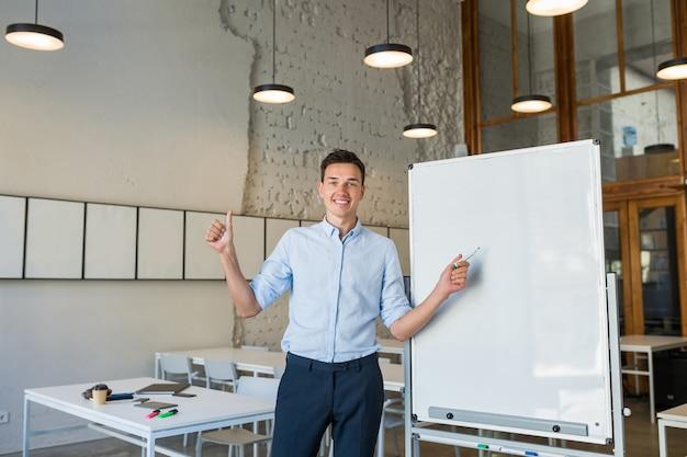 Positiver junger hübscher lächelnder mann, der an leerer weißer tafel mit markierung steht,