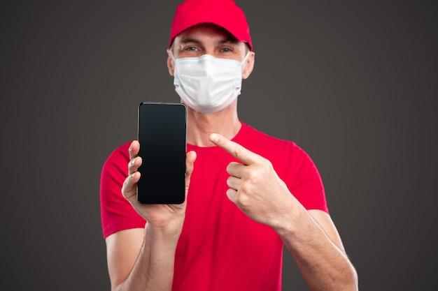 Positiver junger lieferbote in roter uniform und schutzmaske, die smartphone zeigt und app für die online-bestellung von lebensmitteln während der coronavirus-epidemie und quarantäne empfiehlt