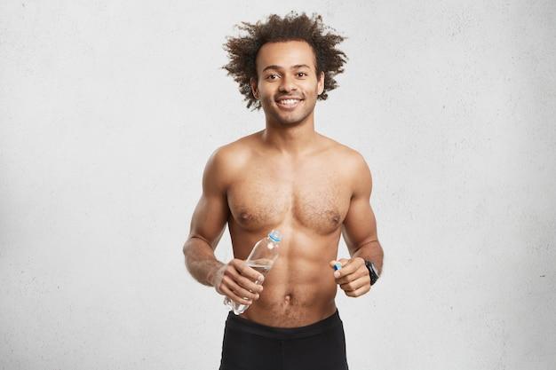 Positiver junger männlicher athlet mit starkem muskelkörper oder rumpf, der nach langem training durstig ist