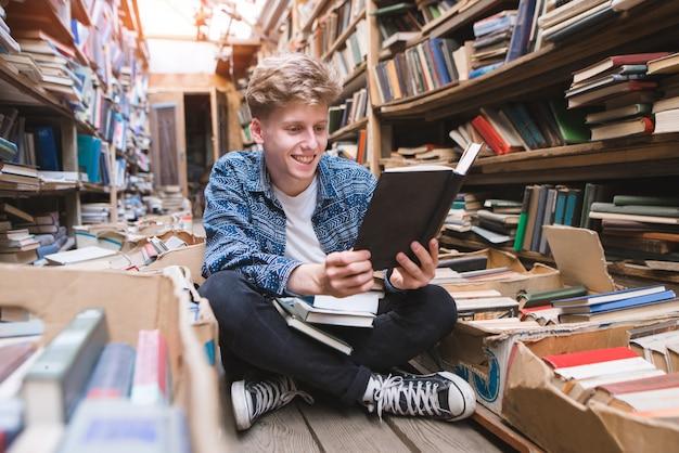 Positiver junger mann, der auf dem boden in einer gemütlichen öffentlichen bibliothek sitzt, bücher liest und lächelt.