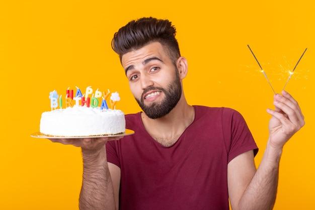 Positiver junger mann, der einen alles- gute zum geburtstagkuchen und zwei brennende bengalische lichter hält, die auf einer gelben oberfläche aufwerfen. platz für werbung