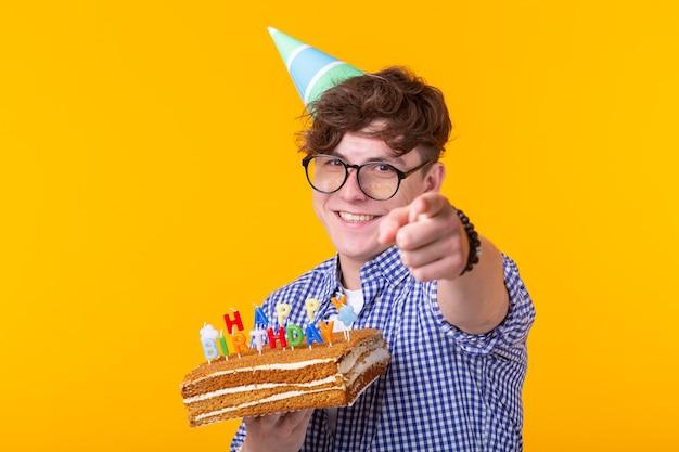 Positiver junger mann, der einen alles- gute zum geburtstagkuchen und zwei brennende bengalische lichter hält, die auf einer gelben wand aufwerfen. platz für werbung