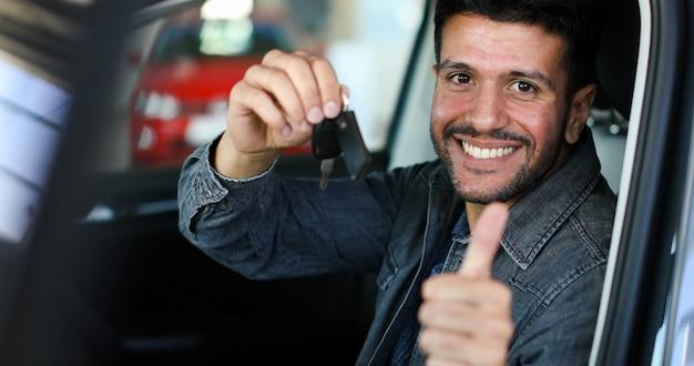 Positiver junger mann, der einen schlüssel sitzt in einem auto mit dem daumen oben hält
