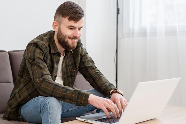 Positiver junger mann, der genießt, von zu hause aus zu arbeiten