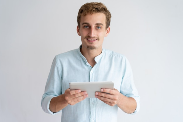 Positiver junger mann, der tablet-computer hält