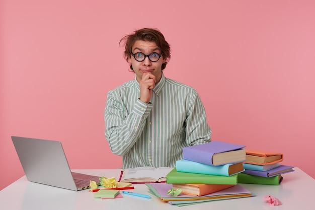 Positiver junger mann mit wildem haar sitzt am arbeitstisch mit büchern und laptop, posiert in hemd und brille, hält kinn mit der hand und schaut mit hochgezogenen augenbrauen