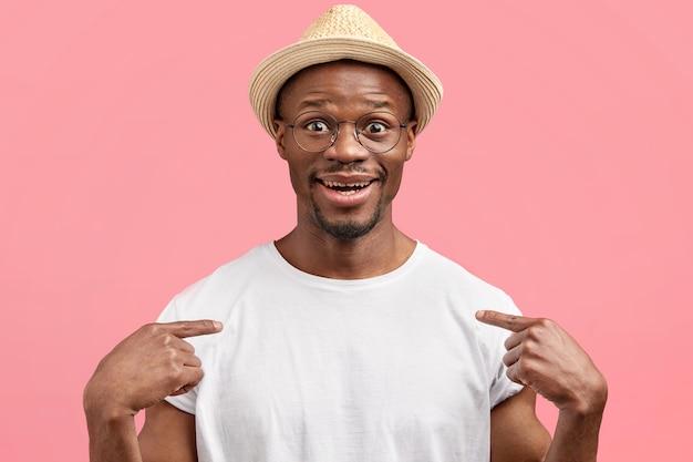 Positiver junger mann mit zufriedenem ausdruck, wirbt für neues lässiges t-shirt