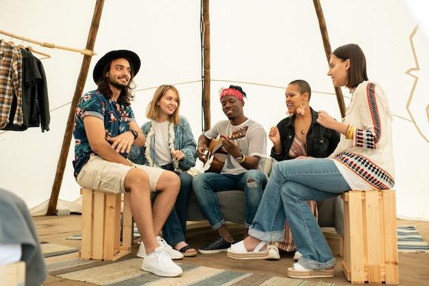 Positiver junger musiker, der gitarre spielt und lied mit freunden im zelt singt