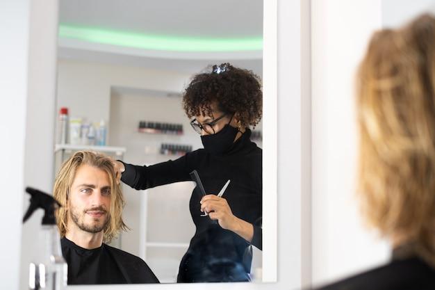 Positiver junger schwarzer friseur, der genießt, im schönheitssalon zu arbeiten und haare des kunden zu föhnen