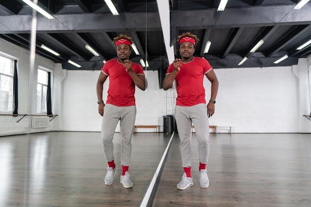 Positiver junger tänzer, der als choreograf arbeitet und neue performance lernt