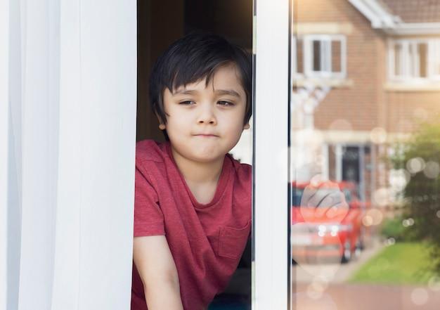 Positiver kinderjunge sitzt am fenster und schreibt auf glas und schaut mit lächelndem gesicht hinaus