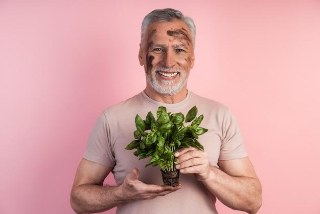 Positiver, lächelnder bauer, der grün in seinen händen hält