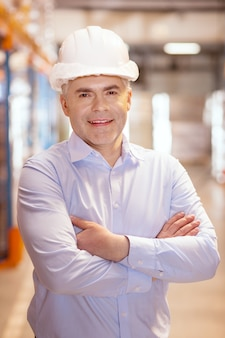 Positiver lagerarbeiter, der lächelt, während er über seinen job glücklich ist