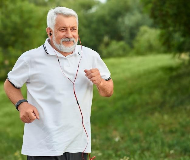 Positiver laufender alter mann im grünen stadtpark.