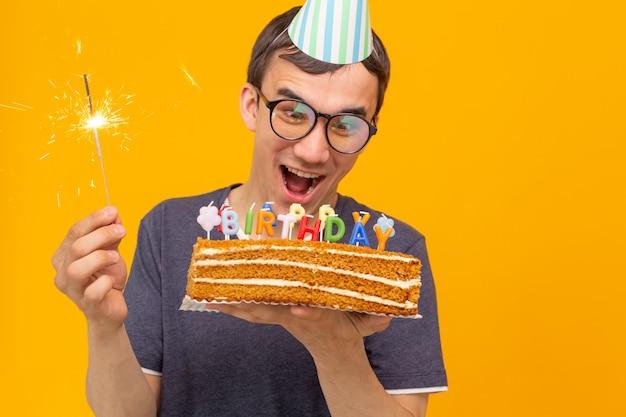 Positiver lustiger junger asiatischer kerl mit einer kappe und einer brennenden kerze und einem hausgemachten kuchen in seinen händen