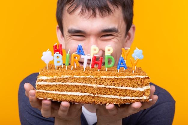 Positiver lustiger junger asiatischer kerl mit einer kappe und einer brennenden kerze und einem kuchen in seinen händen, die auf einer gelben oberfläche aufwerfen