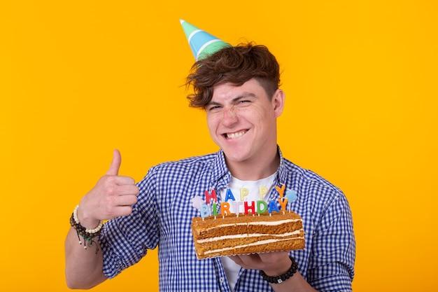 Positiver lustiger junger mann mit einer kappe und einem hausgemachten kuchen in seinen händen, die auf einer gelben wand aufwerfen