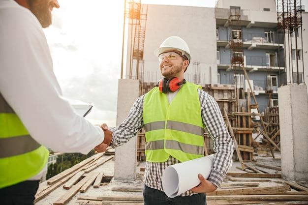 Positiver männlicher baumeister mit blaupause, die hand des erntepartners schüttelt, während er während der arbeit nahe unvollendetem gebäude steht