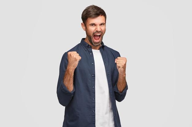 Positiver männlicher champion mit fröhlichem ausdruck, fühlt sich überglücklich über den erreichten erfolg und den gewonnenen wettbewerb, ruft mit weit offenem mund aus, ballt die fäuste, trägt modische kleidung, ist auf weiß isoliert