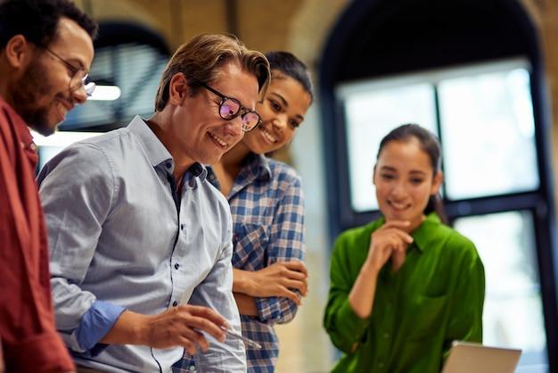 Positiver männlicher chef, der projektergebnisse bespricht und ideen mit jungen motivierten multi-ethnien teilt
