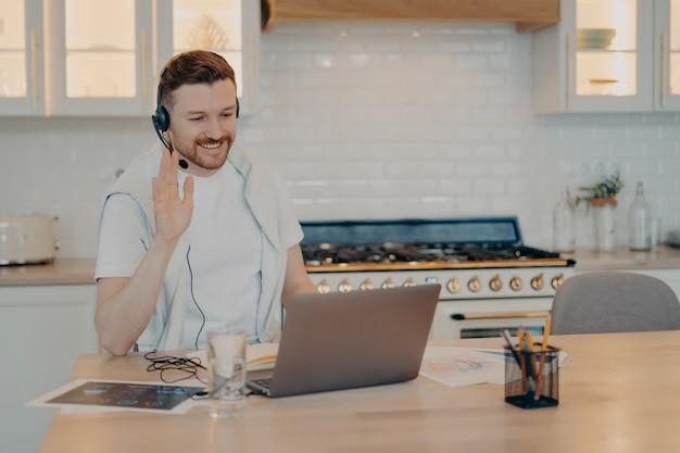 Positiver männlicher freiberufler, der während der online-konferenz mit kollegen zu hause einen laptop verwendet, während er ihnen zuwinkt und auf den bildschirm schaut und an seinem arbeitsplatz im home office sitzt. freiberufliches konzept