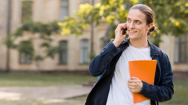 Positiver männlicher student, der am telefon spricht