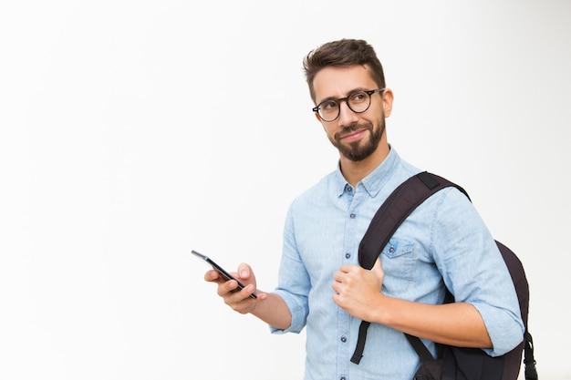 Positiver männlicher tourist mit rucksack unter verwendung des handys