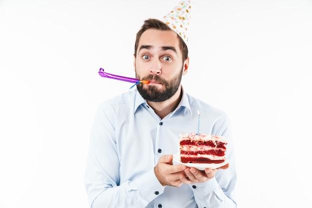 Positiver mann bläst partyhorn und hält geburtstagstorte mit kerze isoliert über weißer wand