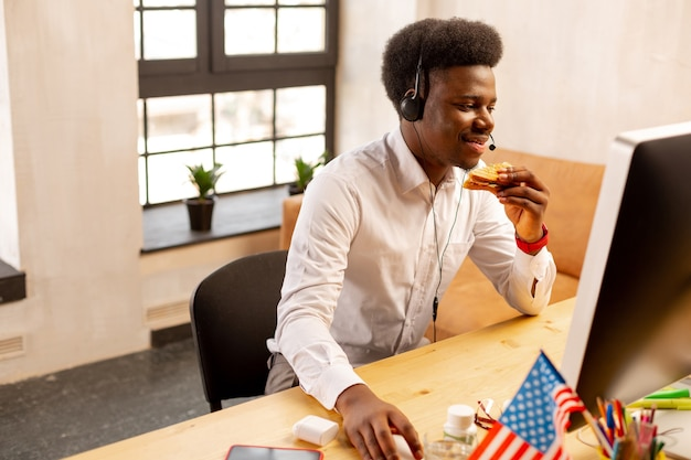 Positiver mann, der auf den pc-bildschirm schaut, während er bereit ist zu arbeiten
