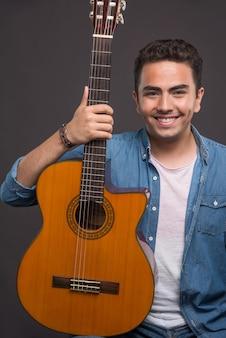 Positiver mann, der eine schöne gitarre auf schwarzem hintergrund hält. hochwertiges foto
