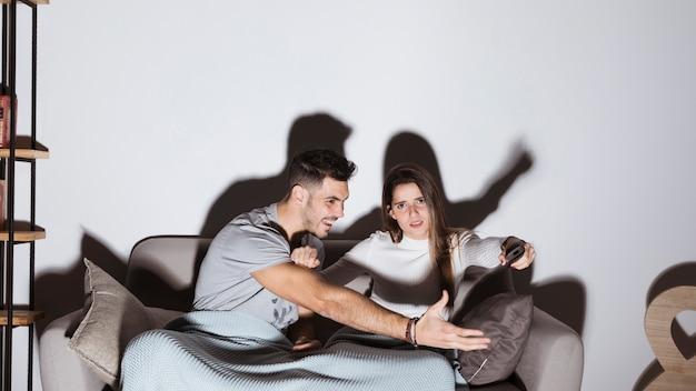 Positiver mann, der heraus hand zum fernsehapparat entfernt von der frauenhand auf sofa erreicht