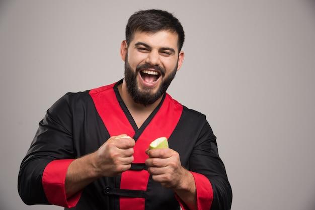 Positiver mann, der in händen zwei scheiben zucchini hält.