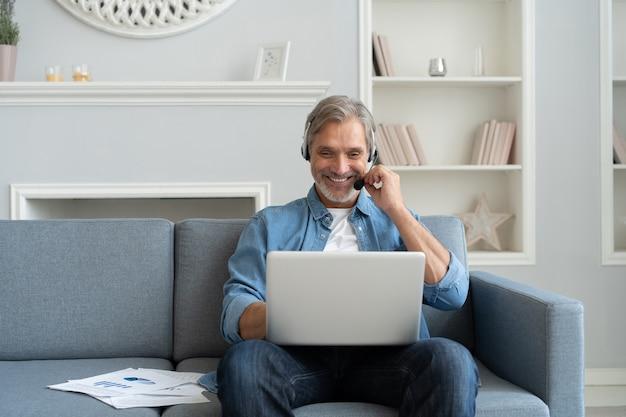 Positiver mann in kopfhörern mit laptop, der podcasts hört oder an einem webinar teilnimmt, das zu hause auf dem sofa sitzt.