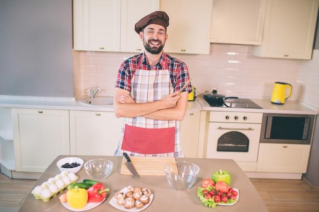 Positiver mann lächelt und lacht. er hält holzgeräte in der hand. auch kerl hält die hände gekreuzt. er ist gut gelaunt. guy ist bereit zu kochen.