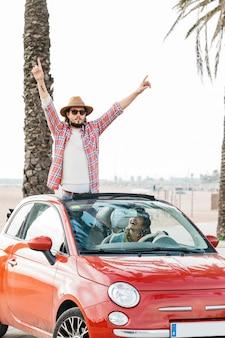 Positiver mann mit den angehobenen händen, die sich heraus vom auto und von der lächelnden frau im auto lehnen