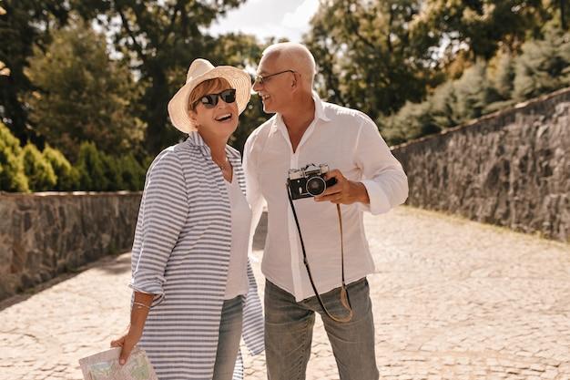 Positiver mann mit grauem haar in hellem hemd und jeans mit kamera, die mit blonder dame im hut, sonnenbrille und gestreiftem blauem hemd im park lacht.