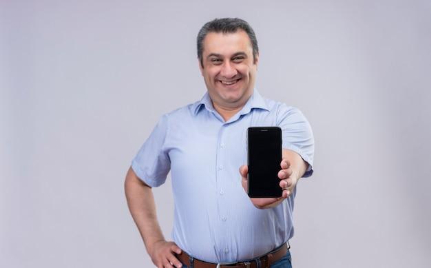Positiver mann mittleren alters, der blaues vertikales gestreiftes hemd trägt, das sein smartphone zeigt, während auf einem weißen hintergrund steht