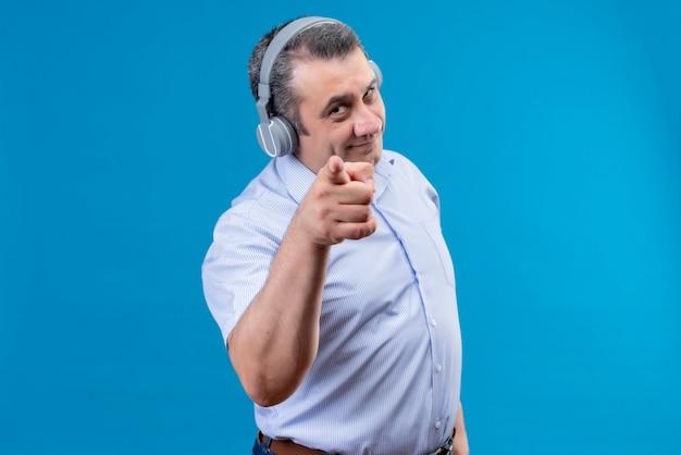 Positiver mann mittleren alters im blau gestreiften hemd, das kopfhörer zeigt zeigefinger auf kamera auf einem blauen hintergrund zeigt