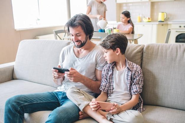 Positiver mann sitzt auf dem sofa und spielt am telefon