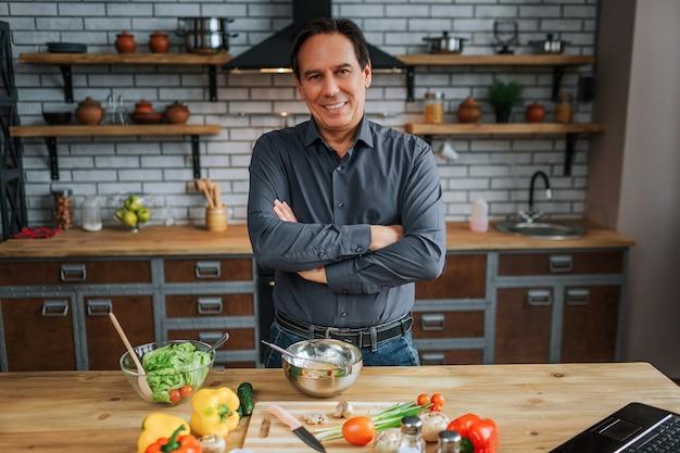 Positiver mann steht am tisch in der küche und posiert vor der kamera. er drückt die hände. buntes gemüse, das auf schreibtisch liegt.