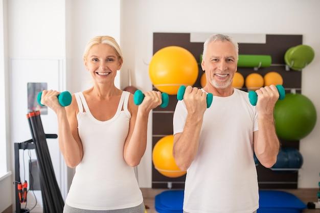 Positiver mann und frau, die mit hanteln im fitnessstudio trainieren