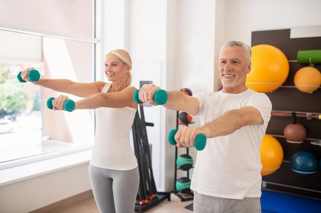 Positiver mann und frau, die mit hanteln trainieren und ihre arme ausstrecken